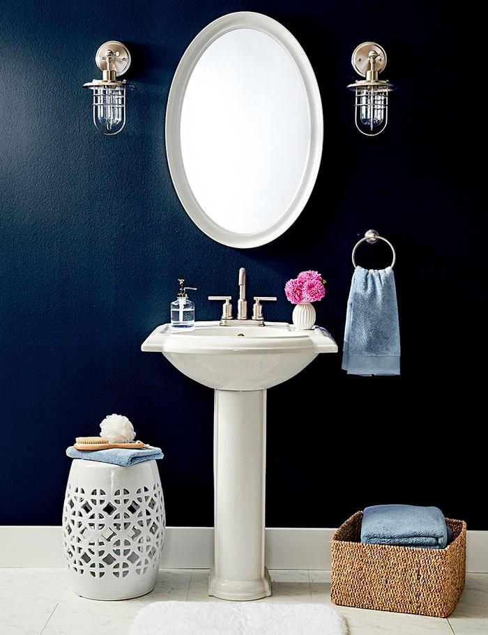 Gương và chậu rửa mặt có màu trắng kết hợp cùng màu xanh của tường